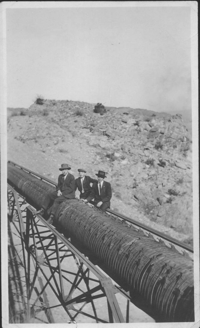 Men sitting on pipeline (L-R: Charlie, F.C. Patterson, Ike), ca. 1915, Copyright Royal Gorge Regional Museum & History Center