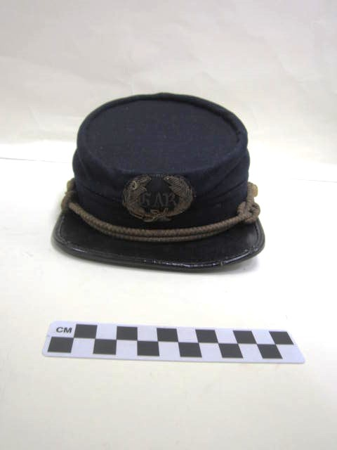 """A navy-blue service cap or kepi with a black rim and 2 gold buttons and gold rope across the brim.  The """"GAR"""" emblem is on the front.  A circular label reads, """"Wanamaker Brown, Philadelphia."""" Belonged to Captain B.F. Rockafellow, 1886. Object ID: 2001.328.002; Royal Gorge Regional Museum & History Center Collection"""