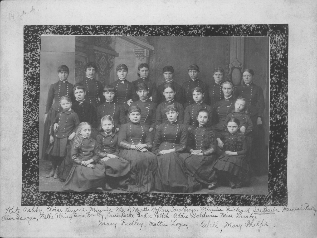 A grayscale cabinet photograph of a group of young girls and teachers in cadet uniforms of the Colorado Collegiate and Military Institute.  The girls are identified: Kate Ashby, Eloise L. Lemons, Minne Mack, Myrtle McClure, Sara Frazer, Minnie Rickard, Ida Barber, Hannah Pedley, Olive Sawyer, Nellie Alling, Fannie Bowlby, Carrie Locke, Sadie Felch, Addie Baldwin, Miss Larabie, Mary Pedley, Mattie Logan, ? Odell, and Mary Phelps, plus three other unidentified girls, 1885. Object ID: 1954.012.005; Copyright Royal Gorge Regional Museum & History Center