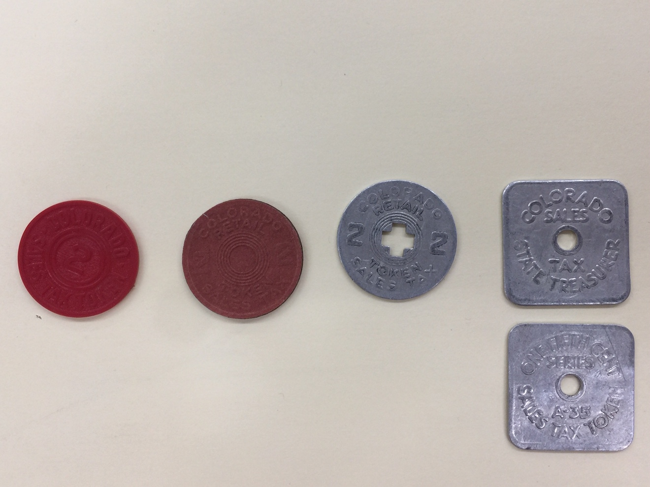 Colorado sales tax tokens, years unknown. Object IDs: 1974.010.1482-1486; Royal Gorge Regional Museum & History Center Collection